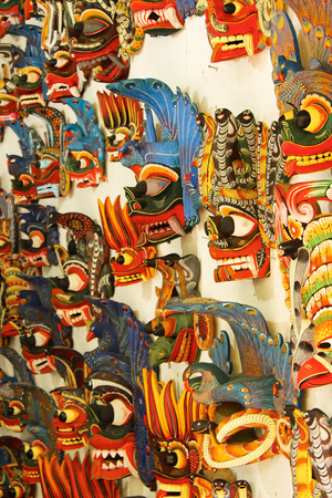souvenir traditional: Traditional totem masks in bright colors with a lot of details, ancient creatures on wall, souvenir shop, travelling photo.