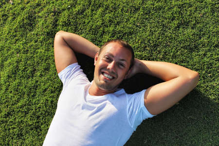 cute guy: Handsome young smiling man outdoor. Funny cute outdoor portrait of happy guy in summer, lying on green grass, relaxing vacation travelling photo. Stock Photo