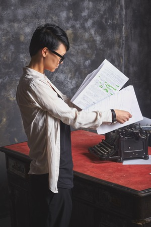 article writing: Young  beautiful woman writer in creative process, reading her work, writing article, art space with grey background ang retro typewriter