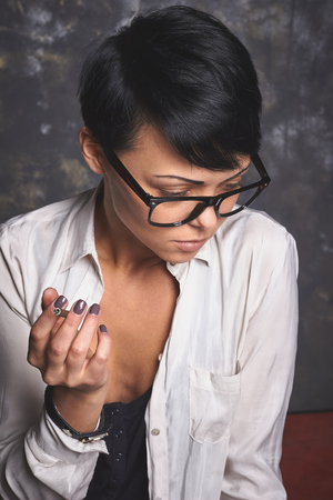 unhealthy thoughts: Young stylish business woman  in glasses and white shirt smoking and thinking, creative process in art space with grey background