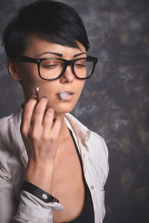 unhealthy thoughts: Young stylish business woman  in glasses and white shirt smoking and thinking, creative process with cigarette, mouthfuls in art space with grey background Stock Photo