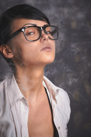 unhealthy thoughts: Young stylish business woman in glasses and white shirt smoking and blowing smoke, hipster girl, grey background