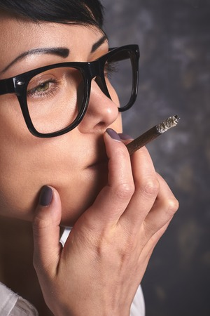unhealthy thoughts: Young stylish business woman  in glasses smoking and thinking, creative process with cigarette, mouthfuls in art space with grey background Stock Photo
