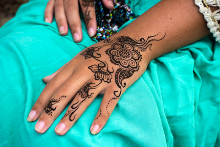 Closeup photo of Female hands with henna tattoo mehndi on bright blue dress, sitting woman in boho style wear, beauty style photography