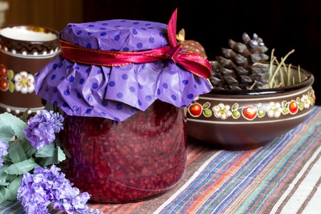 clay craft: photo of sweet raspberry jam-jar, red  ribbon and craft paper,  ukrainian style clay dishes, a sprig of lavender in eco kitchen, food photography