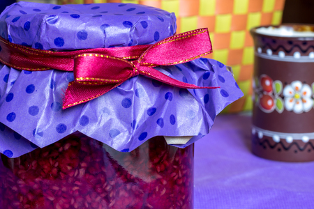 clay craft: photo of sweet raspberry jam-jar, red  ribbon and craft paper, clay cup on purple table in eco kitchen, food photography