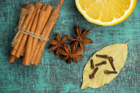 citrus family: Spices and herbs.  Food, cuisine ingredients photography, fresh cinnamon, cloves, anise, lemon on blue painted wooden table. Mulled wine recipe