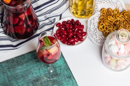Summer home wine with fruits, sangria cocktail, in glass and jar, fresh dogwood berries plate, bright blue background, food photo Stock Photo
