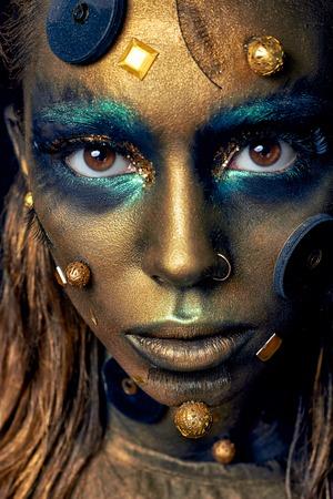 Cosmic insolita trucco con elementi decorativi sul viso, la pelle dorata, concetto creativo trucco, look elegante, studio fotografico