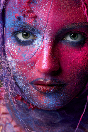 Holi festival colors face art with creative make up. Closeup cropped studio portrait of young fashion model with bright colorful mix of paint. Red, orange, blue body painting. Stock Photo