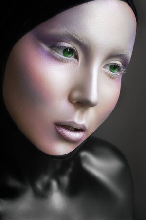 alien women: Portrait of a mysterious woman with a fantastic makeup Alien with green eyes  and silver face, dark black body, cosmo look