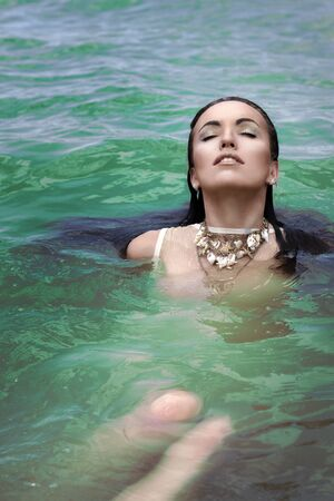 underwater woman: Beautiful girl brunette in green lake swimming in clothes