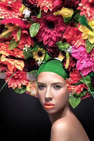 lipgloss: Beauty Girl with Flowers Hairstyle. Beautiful Young Woman Portrait with Summer orange Flowers. Big hat with flowers, Fashion Makeup. Orange lipgloss. Stock Photo