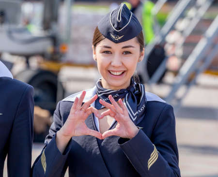 Russia, Vladivostok, 10132017. Beautiful stewardess dressed in official dark blue uniform of Aeroflot Airlines on airfield. Passenger jet aircraft on background. Crew of plane. Aviation and transportation.