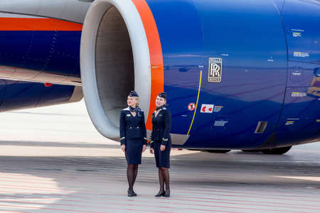 Russia, Vladivostok, 10/13/2017. Beautiful stewardesses dressed in official dark blue uniform of Aeroflot Airlines stand near at Rolls Royce's engine of jet aircraft. Crew of plane. Aviation and transportation. Publikacyjne