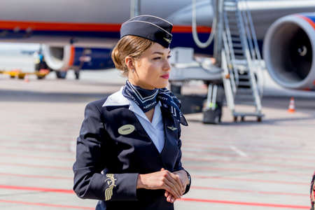 Russia, Vladivostok, 10/13/2017. Beautiful stewardess dressed in official dark blue uniform of Aeroflot Airlines on airfield. Passenger jet aircraft on background. Crew of plane. Aviation and transportation.