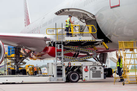 Russia, Vladivostok, 08/10/2018. Passenger airplane Boeing 777-300 of Rossiya Airlines just landed, cargo is unloaded from the aircraft. Service and maintenance of airplanes. Aviation and transportation.