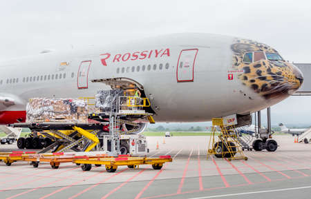 Russia, Vladivostok, 08/10/2018. Passenger airplane Boeing 777-300 of Rossiya Airlines just landed, cargo is unloaded from the aircraft. Fuselage is painted as a face of Far Eastern leopard. Sajtókép