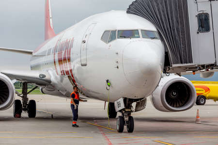 Russia, Vladivostok, 08/10/2018. Passenger airplane Boeing 737 of T'way Air prepares for departure. Engineers check aircraft systems. Service and maintenance of airplanes. Aviation and transportation