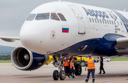 Russia, Vladivostok, 08102018. Passenger airplane Airbus A319 of Aurora Airlines prepares for departure. Engineers check aircraft systems. Maintenance of airplanes. Aviation and transportation. Editorial