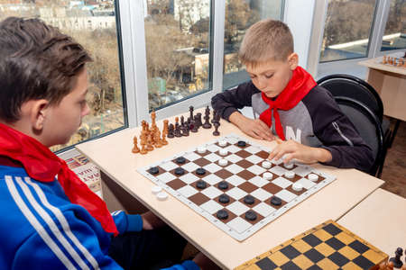 Russia, Vladivostok, 12012018. Kids play chess during chess competition in chess club. Education, chess and mind games. Competition and tournament. Kids leisure.