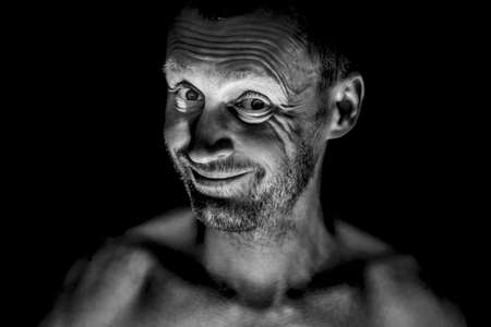 Portrait of unshaven adult caucasian man. He smiles like maniac and seems like madness. Black and white shot, low-key lighting. Isolated on black. Stock Photo