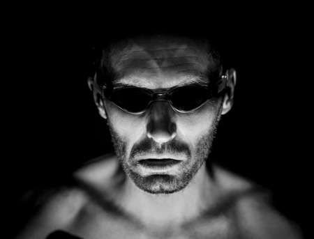 Portrait of unshaven adult caucasian man in swimming glasses. He smiles like maniac and seems like madness. Black and white shot, low-key lighting. Isolated on black. Zdjęcie Seryjne - 134894635