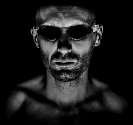Portrait of unshaven adult man in swimming glasses. He smiles and looks like watcher. Black and white shot, low-key lighting. Isolated on black.