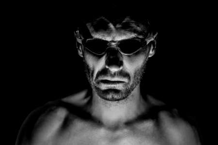 Portrait of unshaven adult caucasian man in swimming glasses. He smiles like maniac and seems like madness or crazy. Black and white shot, low-key lighting. Isolated on black. 写真素材