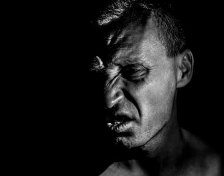 Stylish portrait of adult caucasian man with very angry face and who seems like maniac or devil. He screams at someone. Black and white shot, low-key lighting. Angry man, fear concept.