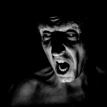 Ritratto alla moda dell'uomo caucasico adulto con la faccia molto arrabbiata e che sembra un maniaco o un diavolo. Urla a qualcuno. Scatto in bianco e nero, illuminazione soffusa. Uomo arrabbiato, concetto di paura.