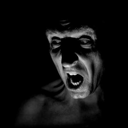 Portrait élégant d'un homme caucasien adulte au visage très en colère et qui ressemble à un maniaque ou à un diable. Il crie sur quelqu'un. Prise de vue en noir et blanc, éclairage discret. Homme en colère, concept de peur. Banque d'images