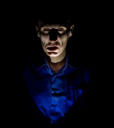 Stylish dark portrait of adult caucasian man who seems like maniac or psycho. Isolated on black background. Low-key lighting.