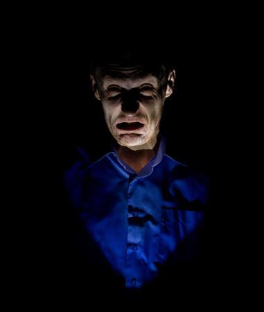 Elegante ritratto scuro di uomo caucasico adulto che sembra maniaco o psicopatico. Isolato su sfondo nero. Illuminazione soffusa.