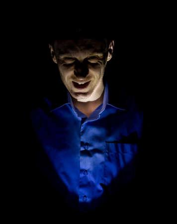 Portrait sombre et élégant d'un homme caucasien adulte qui ressemble à un maniaque ou à un psychopathe. Isolé sur fond noir. Éclairage discret. Banque d'images