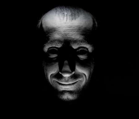 Stilvolles Porträt eines kaukasischen Mannes, der wie ein Wahnsinniger oder Wahnsinniger lächelt. Schwarz-Weiß-Aufnahme.