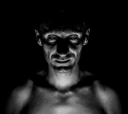 Stylish dark portrait of caucasian man who looks straight at you and looks like maniac. Expressive eyes. Black and white shot, low key lighting. 写真素材