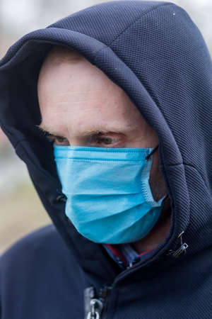 Portrait of caucasian man in medical mask and jacket with a hood to protect himself against COVID-19 and other viruses. Health care and virus protection against COVID-19 during world pandemic.
