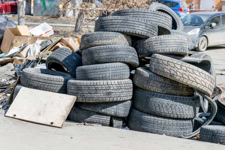 Garbage dump with old discarded car tires in residential area. Dirt and stench, environmental issues. Mud in the streets. City infrastructure and its problems. Bad quality of life. Stockfoto
