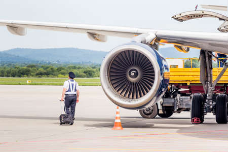 Russia, Vladivostok, 08/17/2020. Captain of passenger jet Airbus A319 near by turbine engine, he checks jet before flight. Plane maintenance and flight safety. Aviation and transportation.