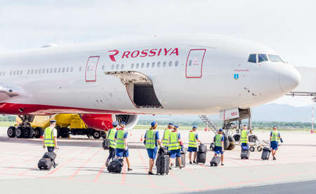 Russia, Vladivostok, 08/17/2020. Crew of airplane in official uniform of Rossiya Airlines goes to board of plane. Plane Boeing 777 of Rossiya Airlines is on background. Aviation and transportation.