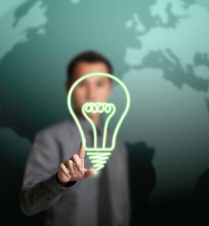business man pointing at alternative green energy saving light bulb symbol photo