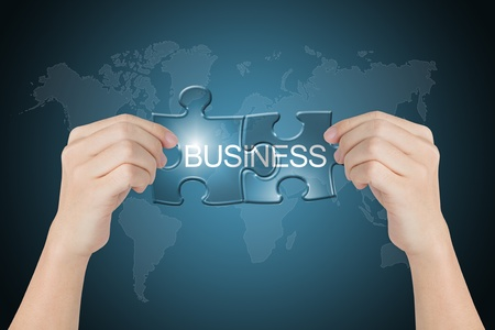 hand holding business connected jigsaw puzzle with world map background photo