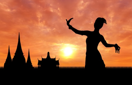 thai dance: woman performing typical thai dance silhouetted with thai style temple background