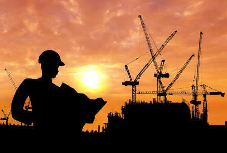 industrial sites: silhouette of a man working on construction site in the morning