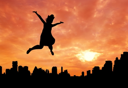 happy girl jumping over city at sunrise