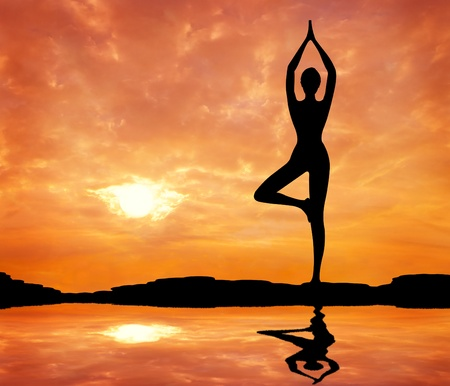 silhouetted of a beautiful woman Yoga in the evening Stock Photo