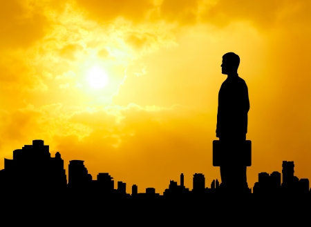 hope: silhouetted business man standing over urban city looking forward and hope success Stock Photo