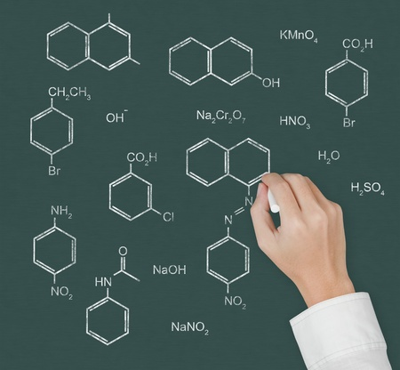 chemistry teacher hand writing scientific  formula of chemical on chalkboard photo