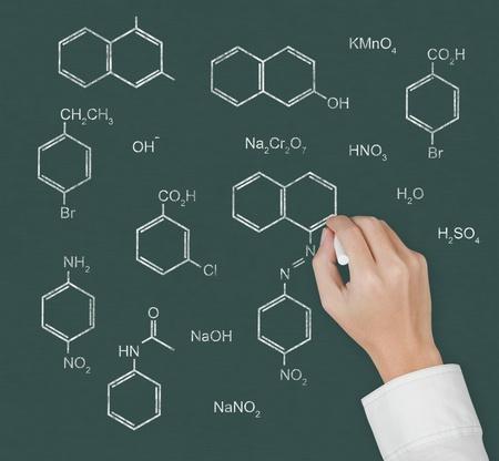 chemistry teacher hand writing scientific  formula of chemical on chalkboard photo